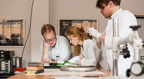 Ein Professor und zwei Studierende beugen sich über eine Filmrolle